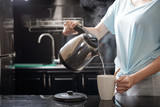 Anonymous female filling mug with hot water while brewing beverage in kitchen - 218198328