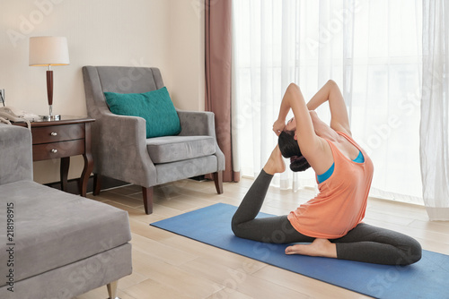 Plakat Side view of young female performing difficult yoga pose while sitting on stretching mat in living room