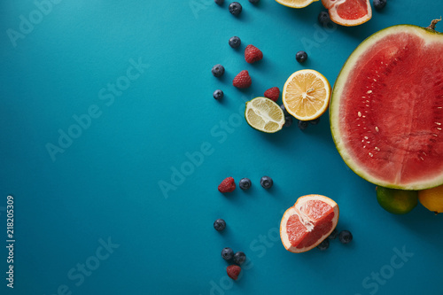 top view of fruits and berries on blue surface
