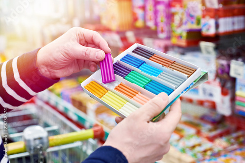 Buyer chooses plasticine in stationery store