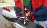 Ein Mann füllt den Tank seines Motorrollers mit Benzin an einer Tankstelle
