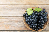Blue grape in basket on grey wooden table - 218261771