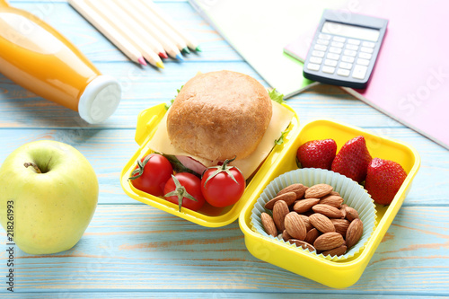 Aluminium Sap School lunch box with sandwich and bottle of juice on wooden table