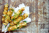 Chicken skewers with pineapple slices with dill and lemon on white paper napkin on an old metal background top view - 218262755