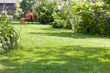 beautiful garden, full of green plants and colorful flowers with an armchair in the background - 218270734