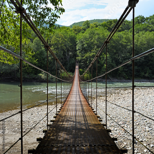 Fototapeta Suspension bridge through river Belaya in Republic of Adygea, Russia