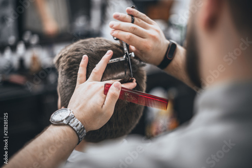 Foto Spatwand Kapsalon Hair Care. Barber makes a haircut with scissors. Soft focus.