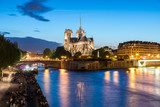 Notre Dame de Paris with cruise ship on Seine river at night in Paris, France