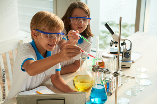Dzieci w wieku szkolnym dodają czerwone i niebieskie płyny do probówki