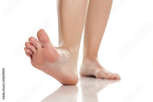 Leinwanddruck Bild female bare feet on white background