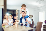 A cheerful family plays board games sitting at a table indoors. - 218335109