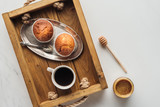 top view of cup of coffee with muffins on tray on white marble - 218335162