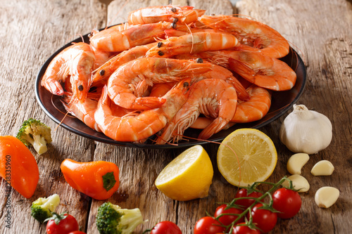 Leinwanddruck Bild Dish with large shrimp and fresh vegetables close-up on a wooden table. horizontal