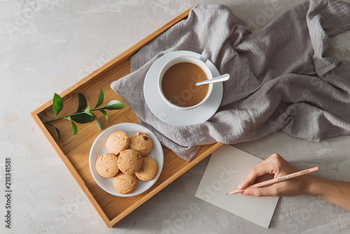 Fototapeta Male hands writing post card on the stone table with cup of coffee and cookie. Business with love concept.
