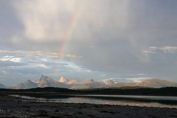 Rainbow over a mountain range in the evening sky