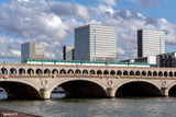 Metro crossing Bercy bridge with National Library of France in background - Paris, France