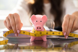 Businesswoman Measuring Piggybank With Measuring Tape - 218365329