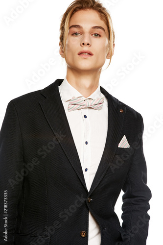 a76b410e79 A handsome young man in a black suit jacket and button up shirt,  accessorized with a ...