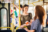 Two beautiful best friends are talking while standing in a bus full of people. - 218386149