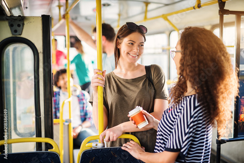 Fototapeta Two beautiful best friends are talking while standing in a bus full of people.