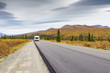 An RV on a deserted road in a colorful autumn landscape dotted with spruce trees and hills at Denali National Park, Alaska