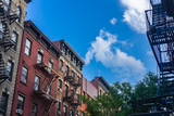 West Village pre-war apartment buildings with blue sky background.