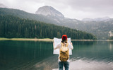 Travel woman with backpack checks map - 218404360