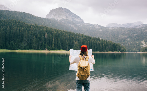 Foto Murales Travel woman with backpack checks map