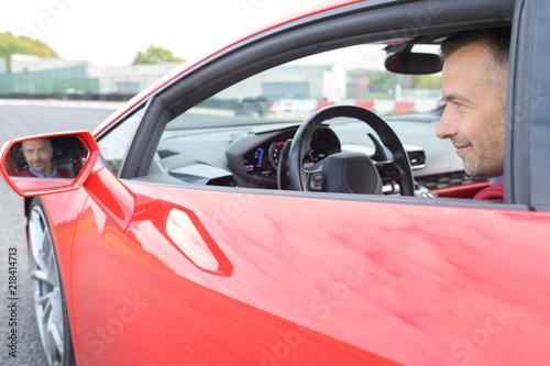 man in sportscar face reflected in wingmirror - 218414713