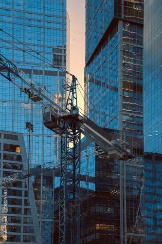 Foto Murales Crane construction bricks concrete building in city downtown skyscrapers