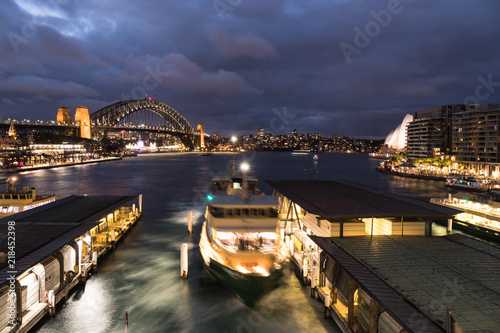 Stunning night view captured with blurred motion of the Circular Quay ferry terminal, the Sydney harbor bridge and the Opera house in Sydney, Australia largest city.