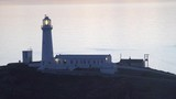 South stack light house Anglesey at dusk with illuminated light rotating - 218452949