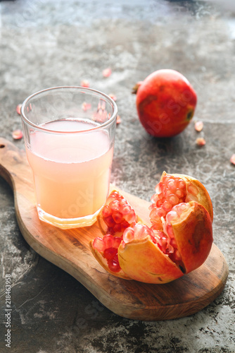 Fototapeta Ripe pomegranate with glass of pomegranate juice on rustic background