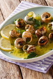 Edible snails, escalgot with butter, herbs and garlic close-up on a table. vertical - 218473760