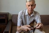 Sad old man holding an empty wallet. - 218494501