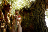 A semi-nude young woman poses inside a large  hollow oak tree. She is dressed only with rags and wears  a thorn wreath on her head. She believes the tree is a sacred place. The woman seen is semi-nude - 218528948