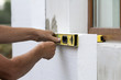 Worker hand with level and knife measuring and cutting white rigid polyurethane foam sheet on wall at newly installed plastic window. Modern technology, renovation, insulation concept.