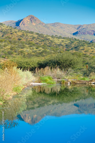 Characteristic hills around Namibian capital Windhoek reflected in calm blue water