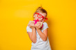 Portrait of an emotional toddler girl in white t-shirt and glasses with gift box on yellow background.