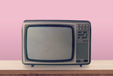 Vintage TV box on wooden table and pink pastel color background. - 218573133