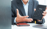 Male arm in suit hold calculator showing calculator in office closeup. Outraged boss shows on the calculator the difference between debit and credit. - 218574720