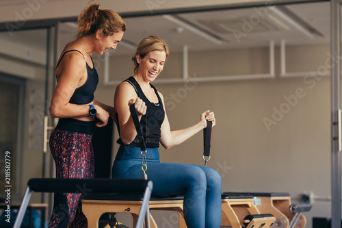Wall mural Smiling women doing pilates workout at the gym