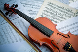 the violin lies on scattered notes - 218588361