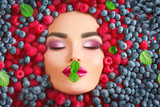 Beauty fashion model girl lying in fresh ripe berries. Face in colorful berries closeup. Beautiful makeup, juicy and sexy lips, pink eyeshadows - 218590969