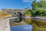 Bridge reflecting in the water of Brecon Canal basin  in Brecon town, Beacons National Park, Wales, UK - 218594766