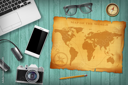 Fototapeta Green wooden table with technology devices and retro map. Travel background.