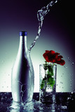 Water pouring on bottle with rose in drinking glass at the side - 218625985