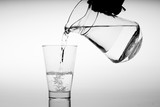 Glass of water with pouring from the bottle, studio shot - 218628986