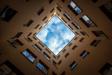 Bottom view of square sky from patio of urban house in Helsinki, Finland, abstract geometric urban background with blue sky and clouds