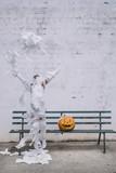 Little mummy boy with a pumpkin sitting in a street bench - 218649933